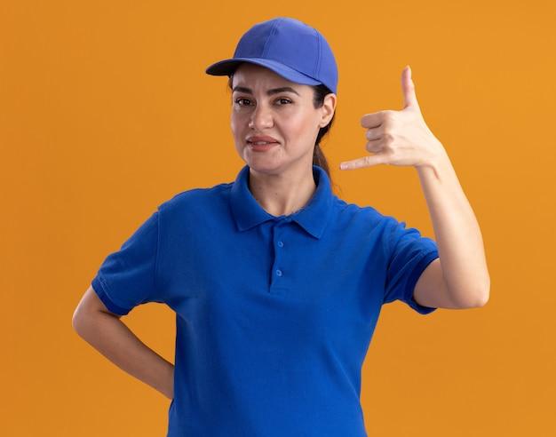 Fiduciosa giovane donna delle consegne in uniforme e berretto che tiene la mano dietro la schiena facendo un gesto sciolto isolato sul muro arancione