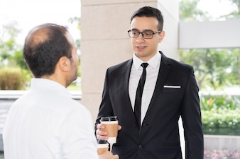 Confident young executive in glasses talking to his colleague