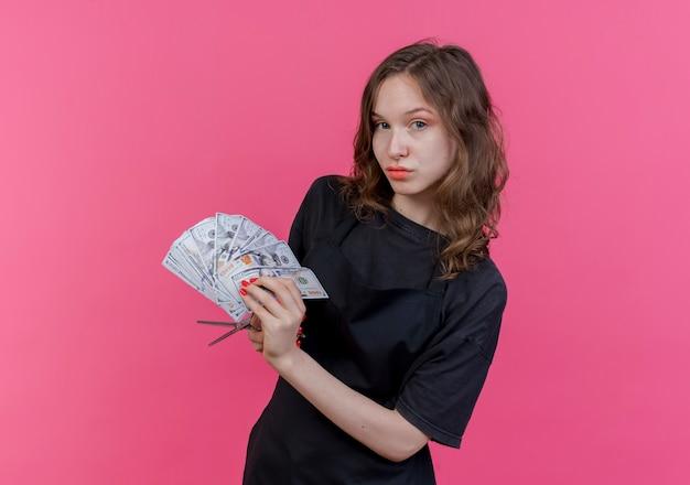 Уверенная в себе молодая женщина-парикмахер в униформе держит деньги и ножницы