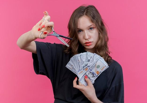 Уверенная в себе молодая женщина-парикмахер в униформе, держащая ножницы и деньги, смотрящую вперед