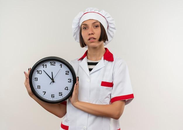 Fiducioso giovane cuoco femminile in uniforme da chef tenendo l'orologio e guardando isolato su bianco con lo spazio della copia