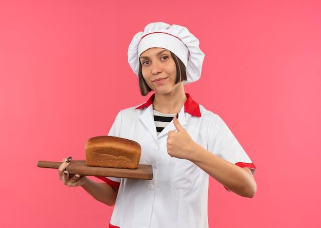 Fiducioso giovane cuoco femminile in uniforme da chef tenendo il tagliere con pane su di esso e mostrando il pollice in alto isolato sul rosa