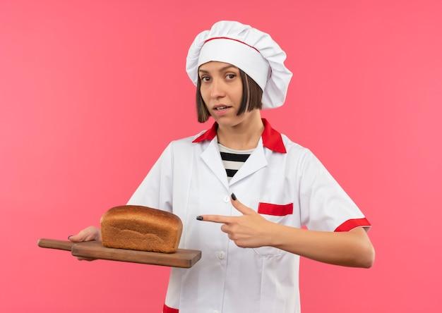 Fiducioso giovane cuoco femminile in uniforme da chef tenendo e indicando il tagliere con pane su di esso isolato sul colore rosa