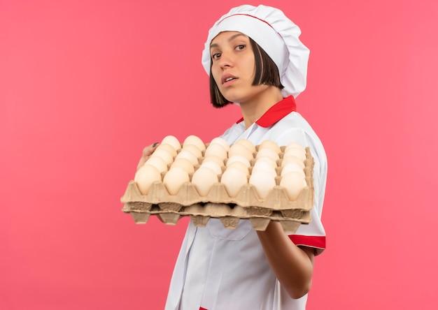 Уверенная молодая женщина-повар в униформе шеф-повара держит коробку яиц, изолированную на розовом, с копией пространства