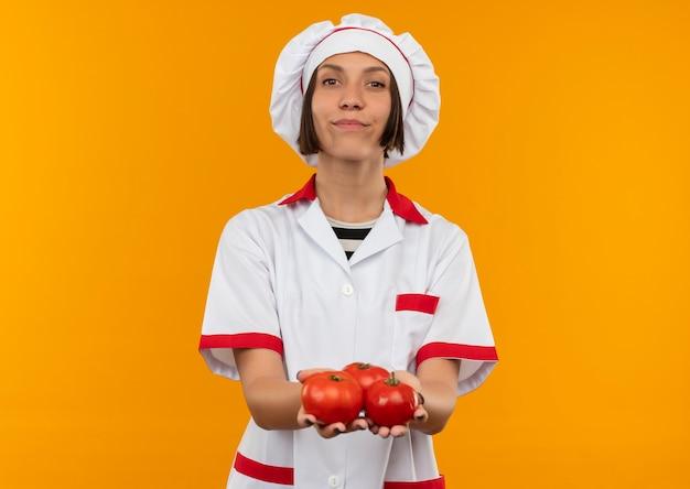 コピースペースでオレンジ色に分離されたトマトを保持しているシェフの制服を着た自信を持って若い女性料理人