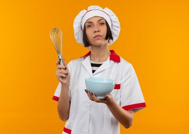 泡立て器とボウルを保持しているシェフの制服を着た自信を持って若い女性料理人がコピースペースでオレンジ色に孤立して見える