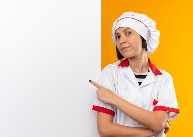白い壁の前に立って、コピースペースでオレンジ色に分離されたそれを指してシェフの制服を着た自信を持って若い女性料理人