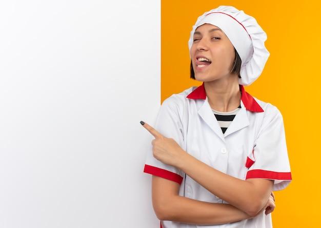 白い壁の前に立って舌を示し、コピースペースでオレンジ色に隔離された壁を指してシェフの制服を着た自信を持って若い女性料理