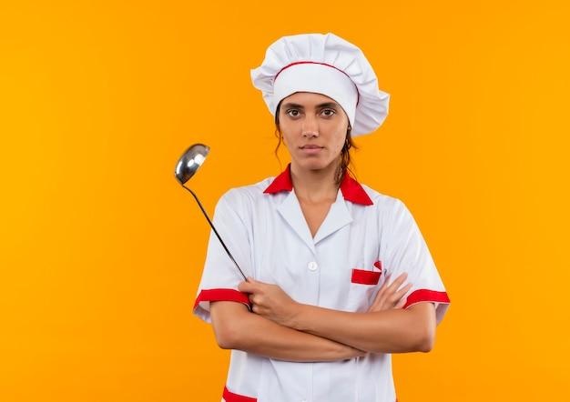 Уверенная молодая женщина-повар в униформе шеф-повара, скрестив руки и держа ковш на изолированной желтой стене с копией пространства