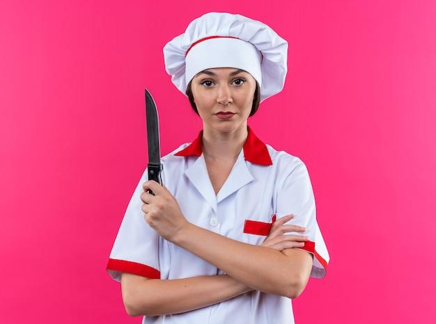 분홍색 배경에 고립 된 칼을 들고 요리사 유니폼 횡단 손을 입고 자신감 젊은 여성 요리사