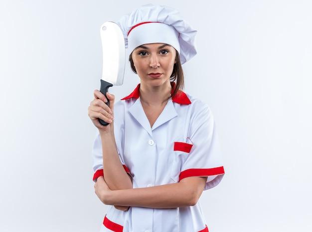 白い壁に分離された包丁を保持しているシェフの制服を着て自信を持って若い女性料理人