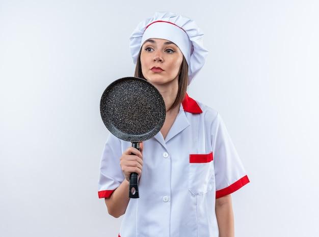 白い壁に分離されたフライパンを保持しているシェフの制服を着て自信を持って若い女性料理人
