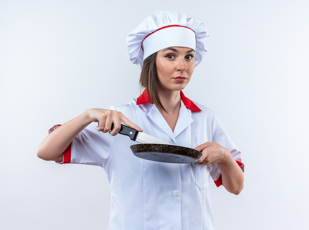 白い背景で隔離のナイフでフライパンを保持しているシェフの制服を着て自信を持って若い女性料理人