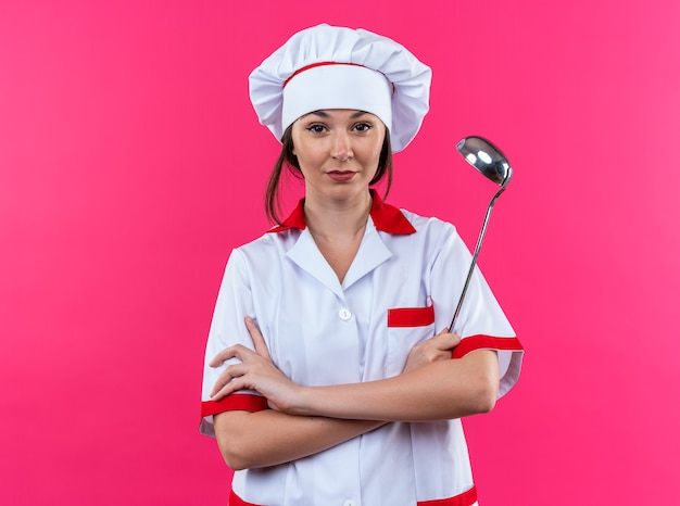 Confident young female cook wearing chef uniform holding ladle crossing hands isolated on pink wall