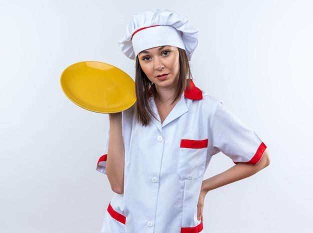 白い背景で隔離の腰に手を置くシェフの制服保持プレートを身に着けている自信を持って若い女性料理人