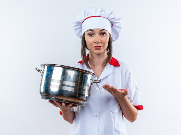 Confident young female cook wearing chef uniform holding and points at saucepan isolated on white wall