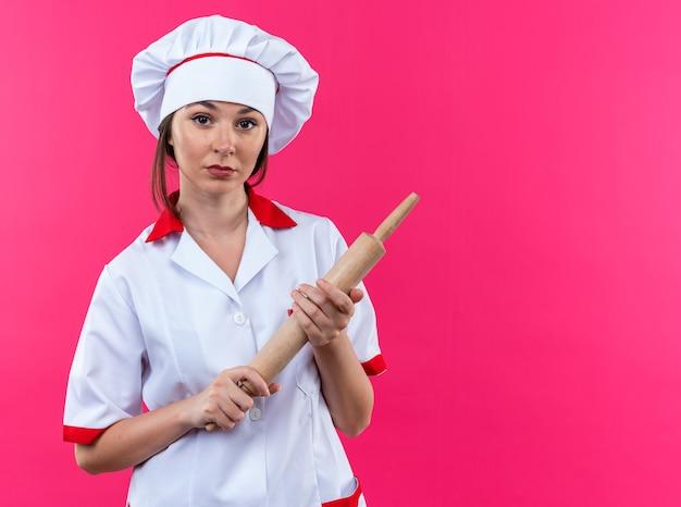 Уверенная молодая женщина-повар в униформе шеф-повара держит скалку на розовом фоне с копией пространства