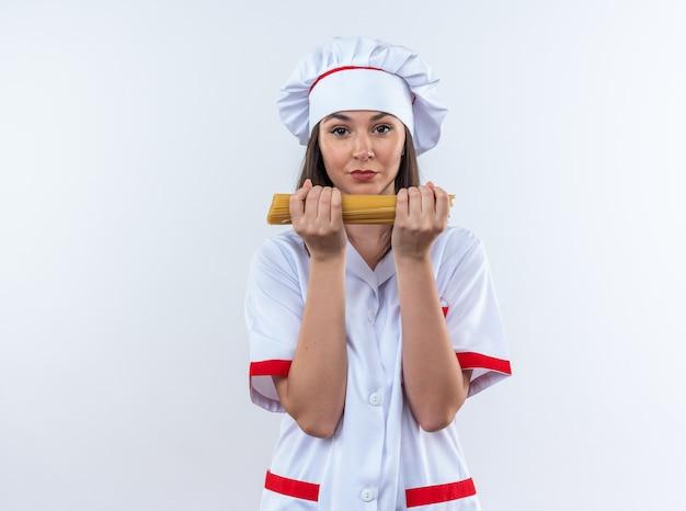 Уверенная молодая женщина-повар в униформе шеф-повара держит спагетти на белой стене