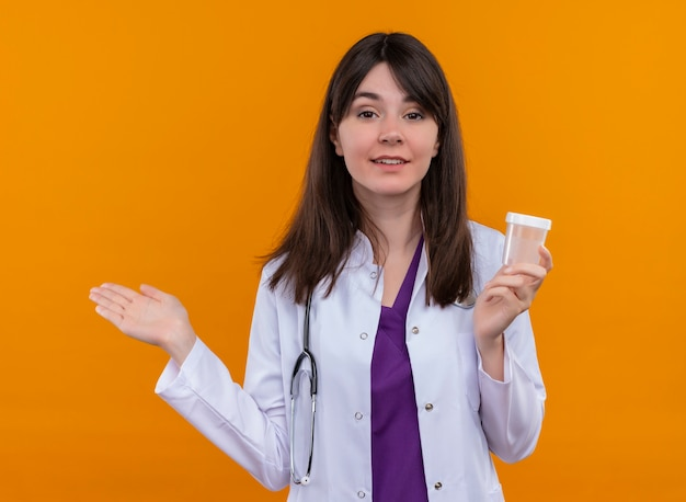 聴診器と医療ローブの自信を持って若い女性医師は、コピースペースで孤立したオレンジ色の背景に薬カップを保持します
