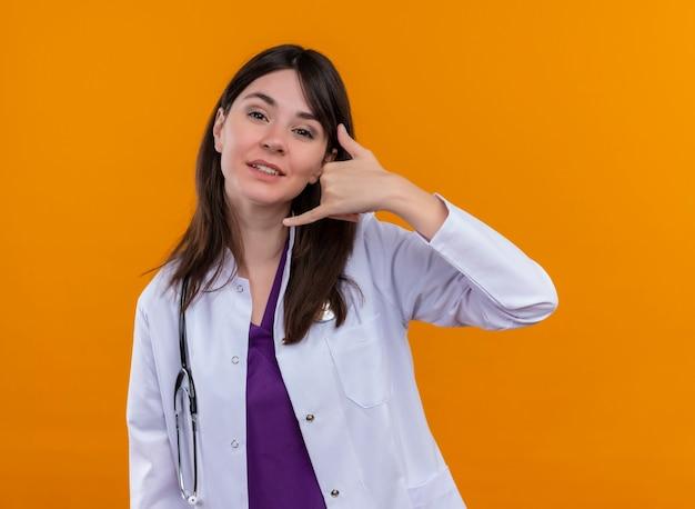 Fiducioso giovane medico femminile in abito medico con gesti dello stetoscopio chiama con la mano su sfondo arancione isolato con spazio di copia