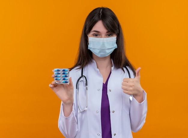 Confident young female doctor in medical robe with stethoscope wears disposable medical face mask holds medicine and thumbs up on isolated orange background with copy space