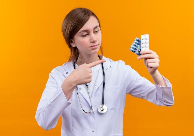 의료 가운과 청진기를 착용하고 의료 약품을 들고 고립 된 오렌지 공간에 그들을 가리키는 확신 젊은 여성 의사