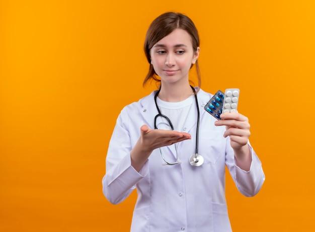 의료 가운과 청진기를 착용하고 의료 약품을 들고 복사 공간이 격리 된 오렌지 공간에 손으로 가리키는 확신 젊은 여성 의사