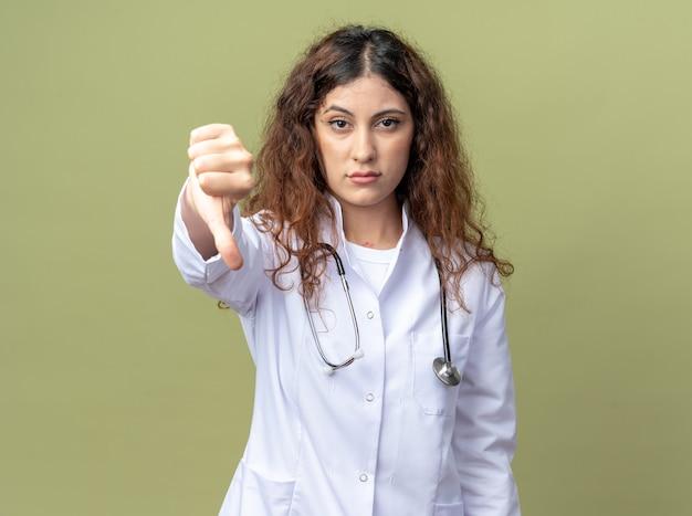 의료 가운과 청진기를 착용한 자신감 있는 젊은 여성 의사는 올리브 녹색 벽에 격리된 엄지손가락을 아래로 보여주는 전면을 보고 있습니다.