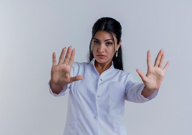 Уверенная молодая женщина-врач в медицинском халате, смотрящая, делает стоп-жест изолирована