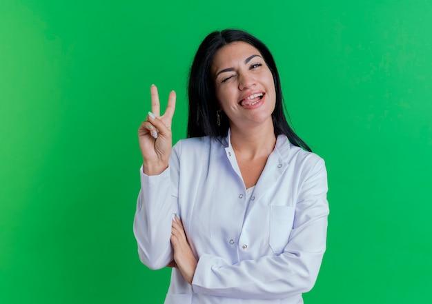 Уверенная молодая женщина-врач в медицинском халате смотрит, подмигивая, показывая язык, делающий знак мира