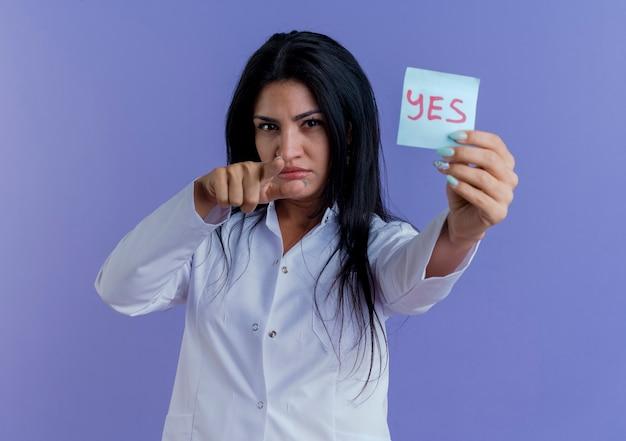 Fiducioso giovane medico femminile che indossa un abito medico che allunga la nota di sì, guardando e indicando