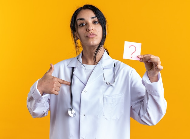 Fiducioso giovane dottoressa che indossa una veste medica con stetoscopio che tiene e punti alla carta per appunti di domanda isolata sulla parete gialla
