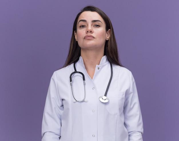 Fiducioso giovane dottoressa che indossa abito medico con stetoscopio isolato sulla parete viola con spazio copia