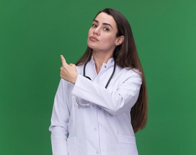 Fiducioso giovane medico femminile che indossa la veste medica con lo stetoscopio punta indietro sul verde