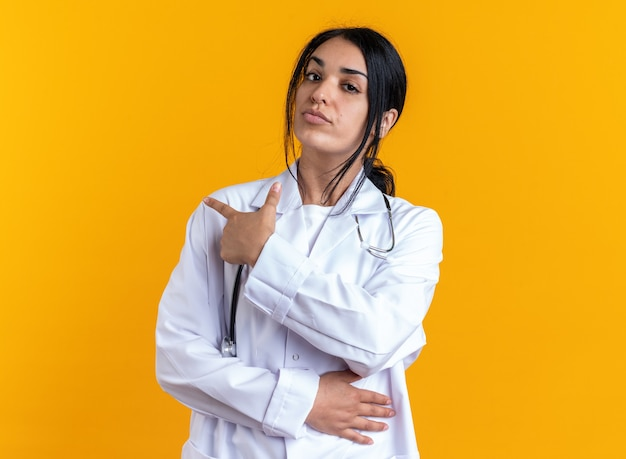 Confident young female doctor wearing medical robe with stethoscope points at behind isolated on yellow wall with copy space