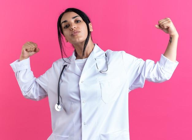 Fiducioso giovane dottoressa che indossa un abito medico con uno stetoscopio che mostra un gesto forte isolato sulla parete rosa