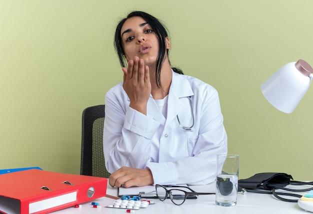 Fiduciosa giovane dottoressa che indossa un abito medico con stetoscopio si siede alla scrivania con strumenti medici che mostrano gesto di bacio isolato su parete verde oliva