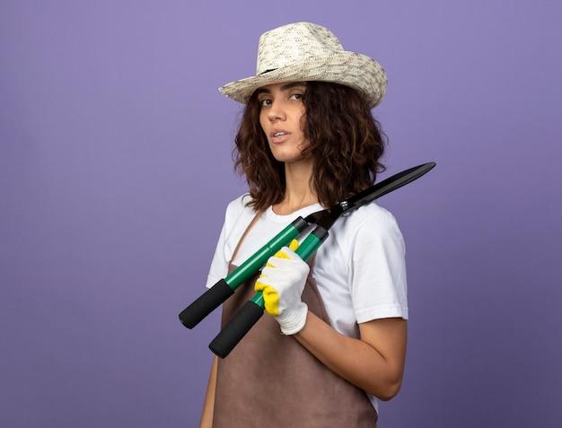 어깨에 가위를 들고 원예 모자와 장갑을 끼고 제복을 입은 자신감이 젊은 여성 정원사