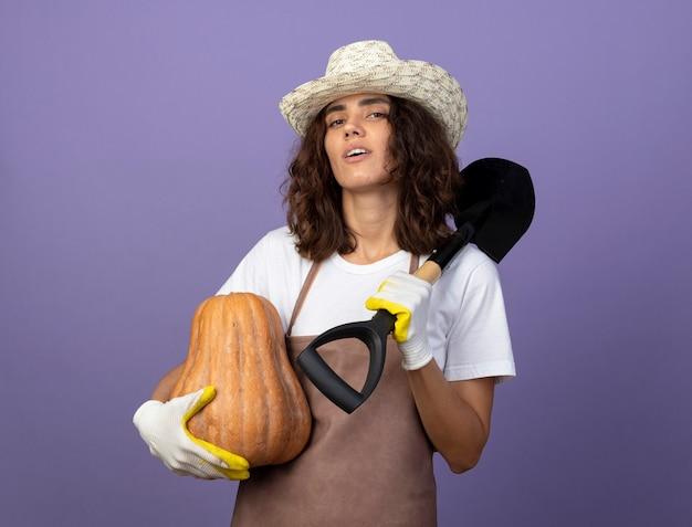 肩にスペードを置くカボチャを保持している園芸帽子と手袋を身に着けている制服を着た自信を持って若い女性の庭師