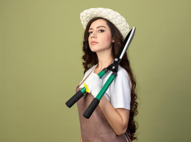 Уверенная молодая женщина-садовник в униформе, садоводческой шляпе и перчатках стоит боком, держа на плече садовые ножницы, изолированные на оливково-зеленой стене