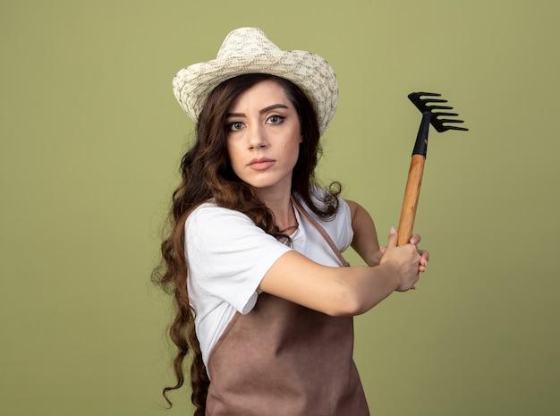 Уверенная молодая женщина-садовник в униформе в садовой шляпе держит грабли на оливково-зеленой стене