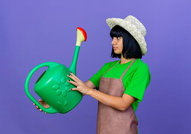 원예 모자를 쓰고 제복을 입은 자신감이 젊은 여성 정원사가 보유하고 물을 수있는 모습
