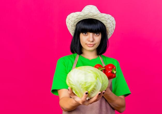 ガーデニング帽子をかぶって制服を着た自信を持って若い女性の庭師はキャベツと赤唐辛子を保持します