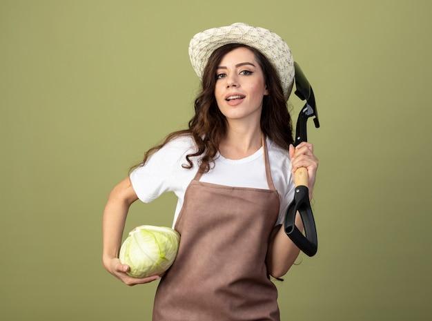 Уверенная молодая женщина-садовник в униформе в садовой шляпе держит капусту и лопату, изолированные на оливково-зеленой стене