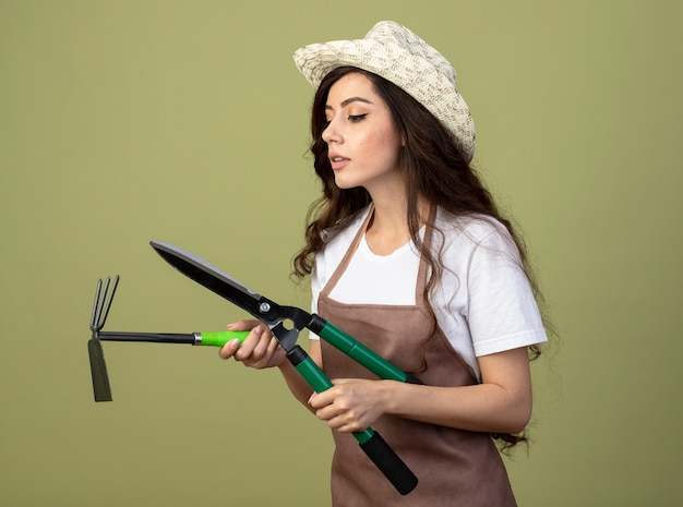 Уверенная молодая женщина-садовник в униформе в садовой шляпе держит кусачки и грабли, изолированные на оливково-зеленой стене