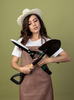 ガーデニング帽子を身に着けている制服を着た自信を持って若い女性の庭師は、オリーブグリーンの壁に分離された交差スペードとクリッパーズを保持します