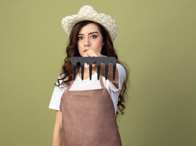 ガーデニング帽子を身に着けている制服を着た自信を持って若い女性の庭師は、オリーブグリーンの壁に分離された熊手を差し出します