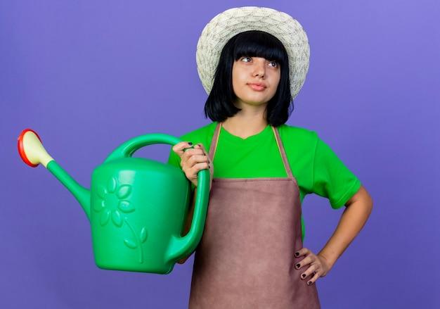 원예 모자를 쓰고 유니폼을 입고 자신감이 젊은 여성 정원사는 물을 수를 보유하고 조회