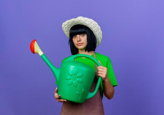 원예 모자를 쓰고 제복을 입은 자신감이 젊은 여성 정원사는 물을 수 있습니다.