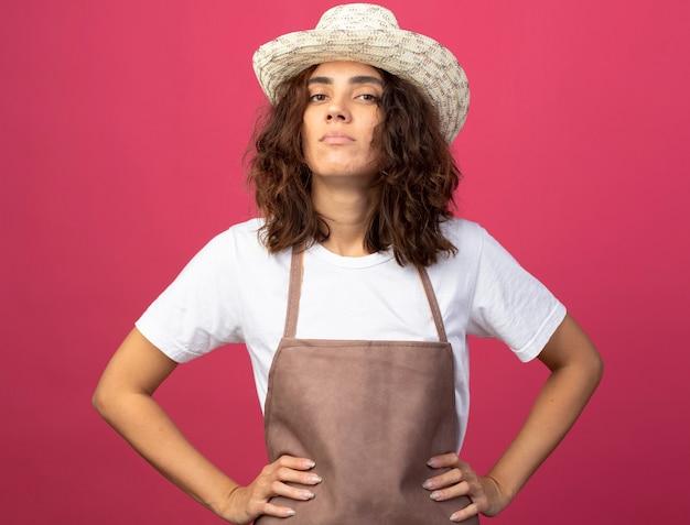 ピンクで隔離の腰に手を置くガーデニング帽子を身に着けている制服を着た自信を持って若い女性の庭師
